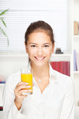 Young smiling woman holding glass of orange juice