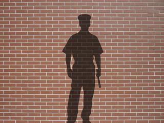 ombre de policier sur briques rouges