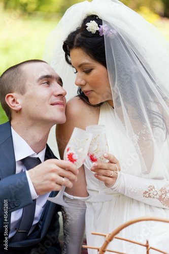 groom and  bride  sit on a grass with champagne glasses