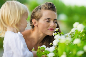 Mother and baby enjoying flowers outdoors
