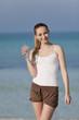 Frau trinkt wasser aus einer flasche am Strand Hochformat