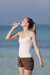 Quadro Frau trinkt wasser aus einer flasche am Strand Hochformat