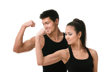 Two sportive people in black sportswear showing their biceps