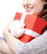 Young woman hands a xmas gift wrapped in red paper, isolated on