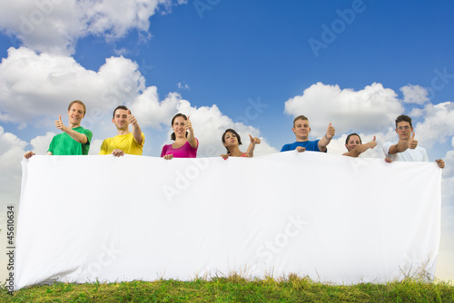 Group of young people holding a big blank paper in nature