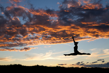 female gymnast jumping in sunset