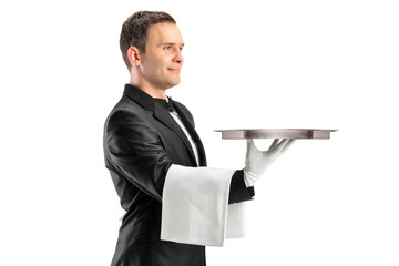 A butler with bow tie carrying an empty tray