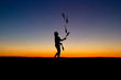 juggler in sunset with five juggling clubs