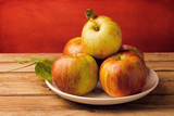 Fresh red apples on wooden tabletop against grunge red wall poster
