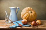 Still life with pumpkin and blue jug on wooden tabletop poster