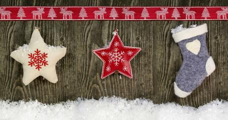 Weihnachtsschmuck auf Holz mit Schleifenband und Schnee