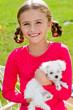 Best friends - happy girl with cute puppy in the garden