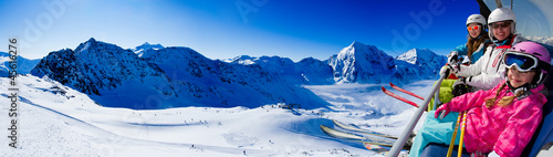 Skiing - happy skiers on ski lift