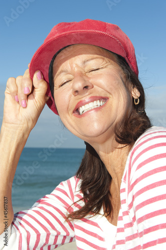 Cheerful mature woman ocean background