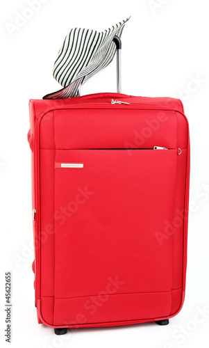 Red suitcase with female sun hat, isolated