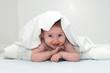 Baby unter Decke lachend