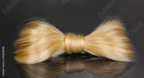 Shiny blond hair-pin on grey background