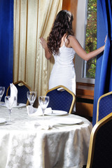 young beautiful woman looking out from window in restaurant