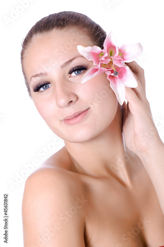 Pretty face of beautiful young woman with lily on hands