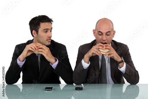 businessmen eating hamburgers