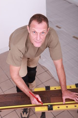 Man at home cutting wooden flooring to size