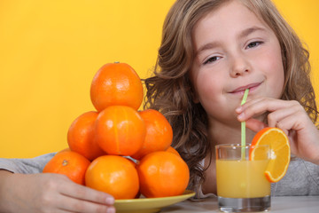 Little girl drinking freshly squeezed orange juice