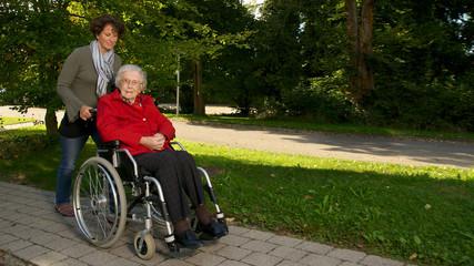 Seniorin im Rollstuhl mit Betreuerin 16:9