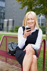Geschäftsfrau mit Smartphone auf Parkbank