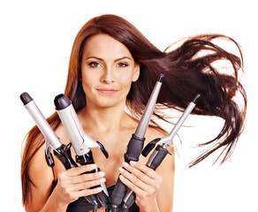 Woman holding iron curling hair.