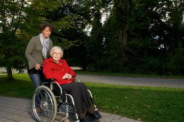 Seniorin wird im Rollstuhl von Betreuerin geschoben