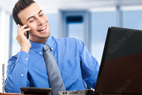 Businessman sitting at the desk and talking at the phone