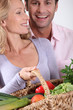 Couple laughing with vegetable basket.