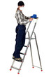 A female painter with a spray gun on a ladder.