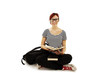 Redhead woman with glasses sitting on floor studying