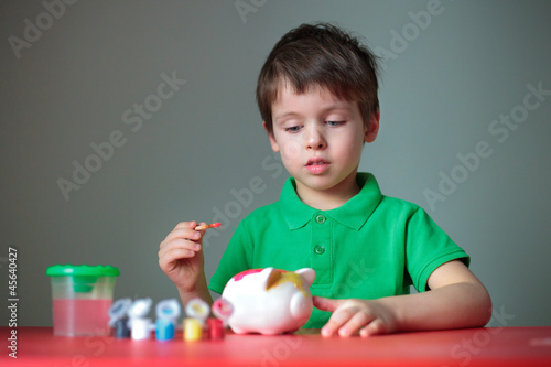Four years old boy painting his piggy toy