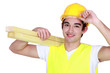 young carpenter with hand to hard hat carrying planks