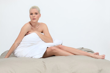 Naked woman sitting on a bed behind a pillow