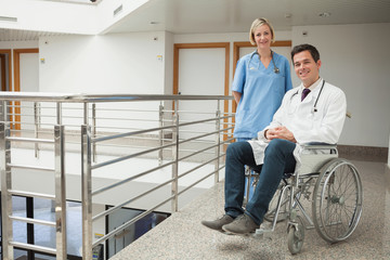 Nurse standing with doctor sitting in wheelchair