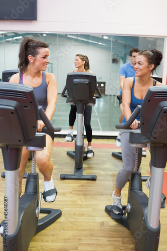 Women talking while training on exercise bike
