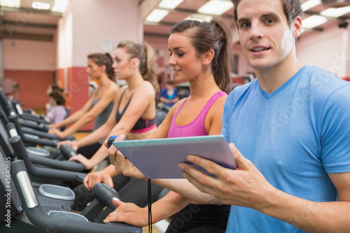 Male gym instructor with women on treadmills