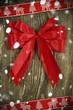 Rote Schleife mit Schleifenband und Schnee auf Holz