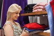 Woman holding clothes at a shelf