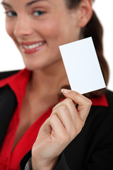 smiling young businesswoman showing business card
