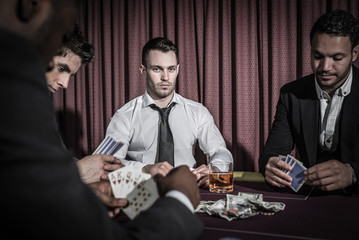 Serious man looking up from high stakes poker game