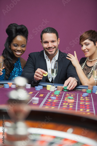 Man playing roulette with two women