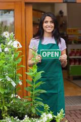 Woman holding open sign at entrance to garden center