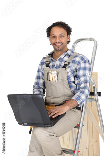 Tradesman leaning against a stepladder and using a laptop