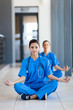 two pretty nurses during meditation during break in hospital