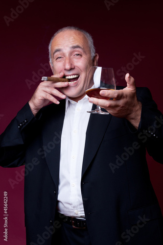 happy senior man with glass and cigar