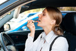 woman sitting in the car and painting her lips
